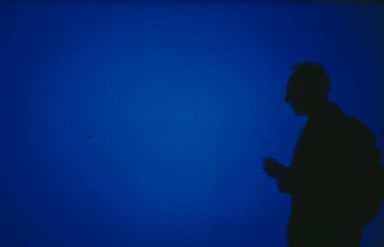Derek Jarman against the background of BLUE (1993). Photography: Liam Daniel. Basilisk Communications
