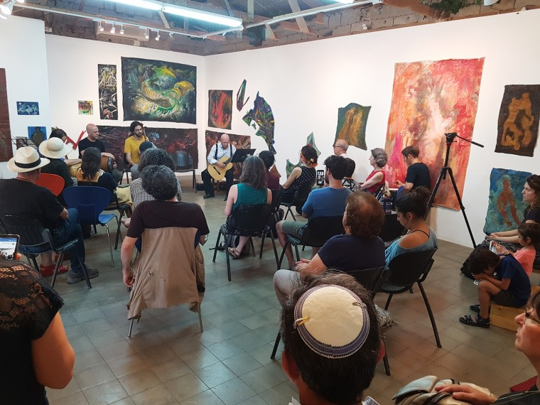"Performance during ""Fugue In Three Voices"" exhibition, featuring works by Roger Ychai (playing guitar), Noga Farchy, & Mia Yankovich Shentser, courtesy of Barbur Gallery"