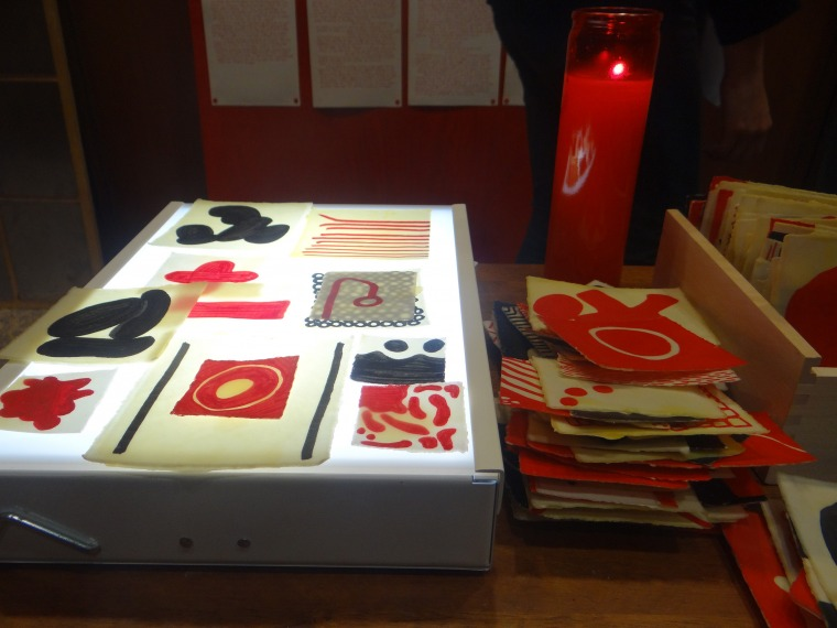 Josh T. Franco. In Tlilli, in Tlapalli: Three Tejanos in Red and Black (detail: Tejano/a Story-telling Table), 2013,  dinner tray, die-cut letters, beeswax-coated glyphs, light table, candle. Mulberry House, San Antonio. photo: Maya Cueva