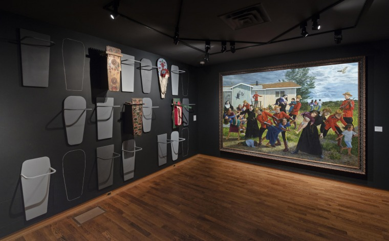 "Installation view of ""Shame and Prejudice: A Story of Resilience"" at the Art Museum at the University of Toronto. Image Credit: Toni Hafkenscheid. Left: Various Cradleboards from the Glenbow Museum Collection. Right: Kent Monkman, The Scream, 2016, Acryli"