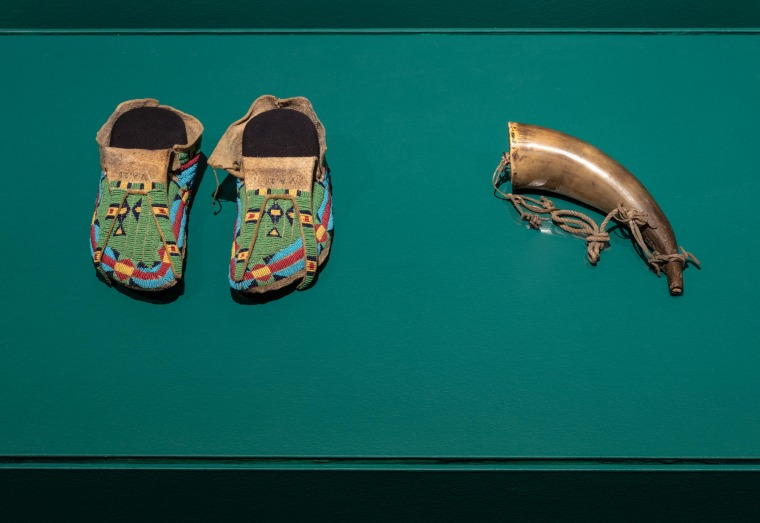 "Installation view of ""Shame and Prejudice: A Story of Resilience"" at the Art Museum at the University  of Toronto. Image Credit: Toni Hafkenscheid. Poundmaker's Moccasins, 1875-1890, Glass beads, painted rawhide from parfleche container, smoked brain-tann"
