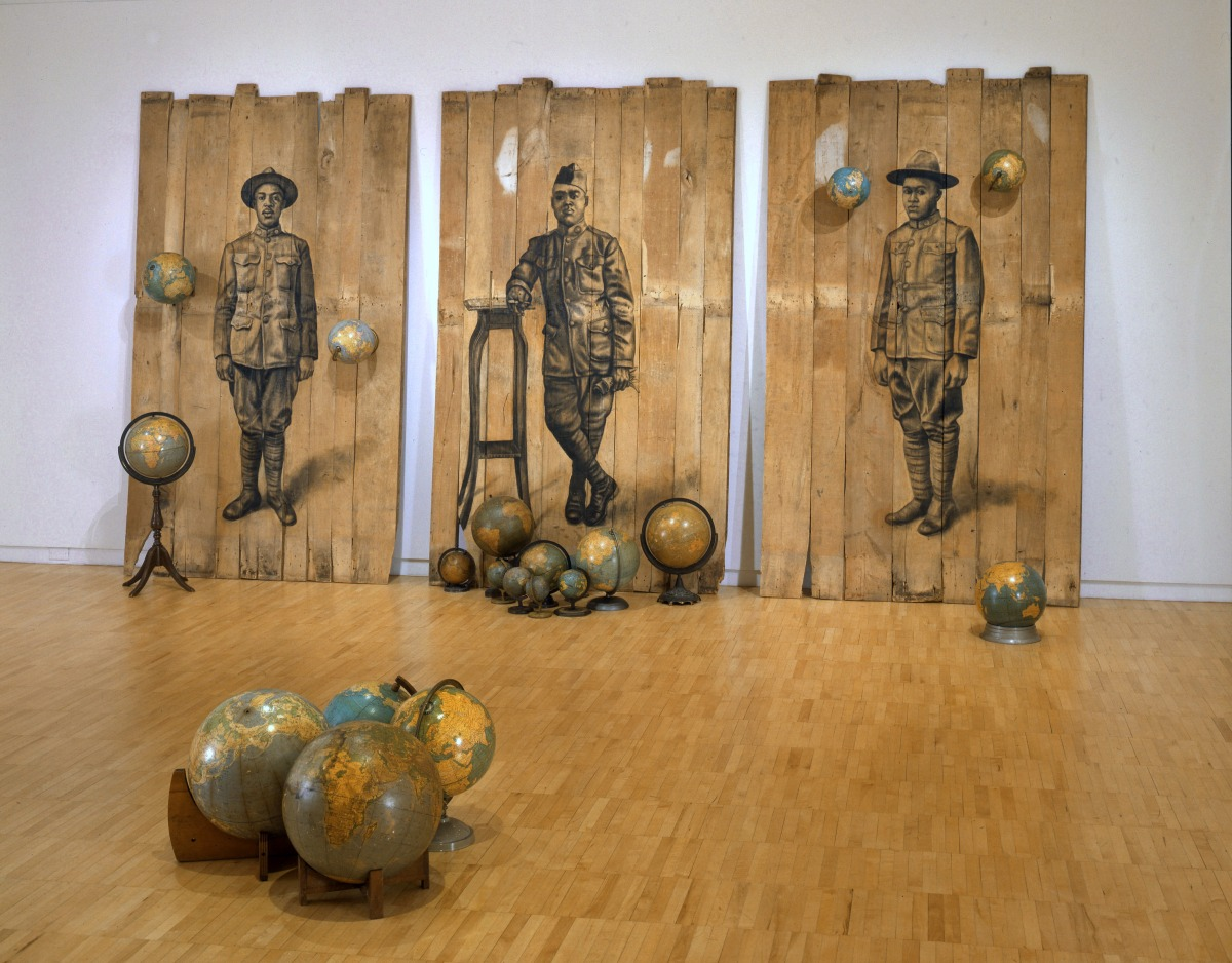 Whitfield Lovell Autour Du Monde, 2008 Conte on wood panels with globes 102 x 189 x 171 inches ©Whitfield Lovell. Courtesy of DC Moore Gallery, New York