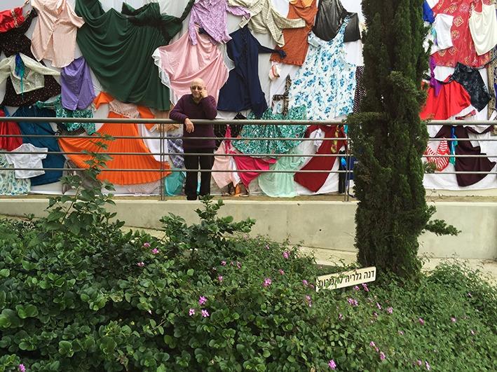 דב אור נר על רקע חזית הגלריה המכוסה בשמלות שנתפרו במתפרת הקיבוץ
