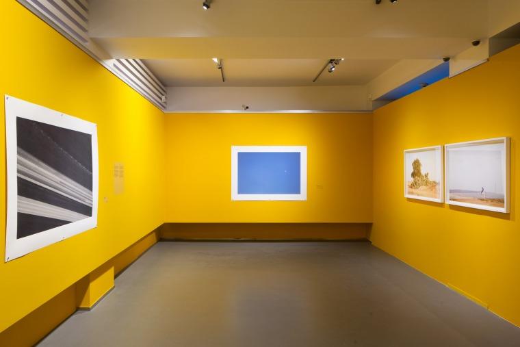 """צילום הצבה, פרט, קומה שניה. משמאל ובמרכז צילומים מהסדרה """"הדרך, איפה זה שם""""; מימין צילומים מגוף העבודה """"חלום המדבר"""""""