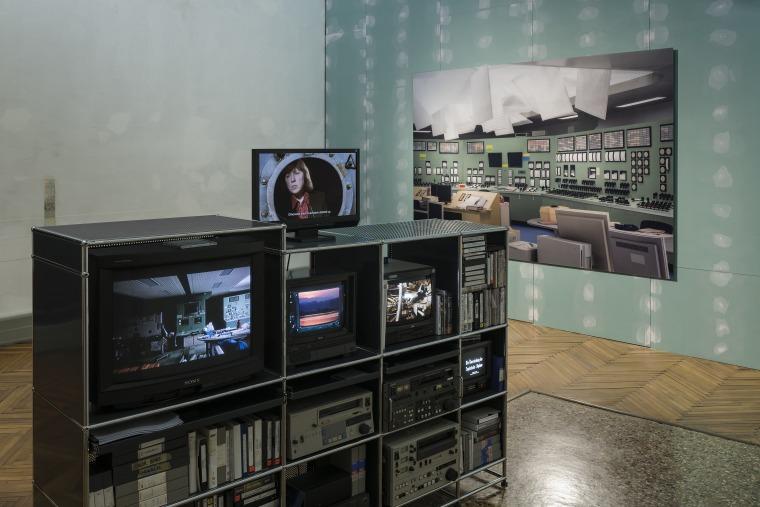 """מראה הצבה של """"הספינה דולפת. הקברניט שיקר."""" (אוצר: אודו קיטלמן), פונדציונה פראדה, ונציה: אנה פיברוק, Media system shelf (מדף מערכת מדיה), 2017; במסך: אלכסנדר קלוגה, Stummfilm mit zwei O-Tonteilen (סרט אילם עם שני מקטעי קול), 2017; על הקיר: תומס דימנד Kontr"""