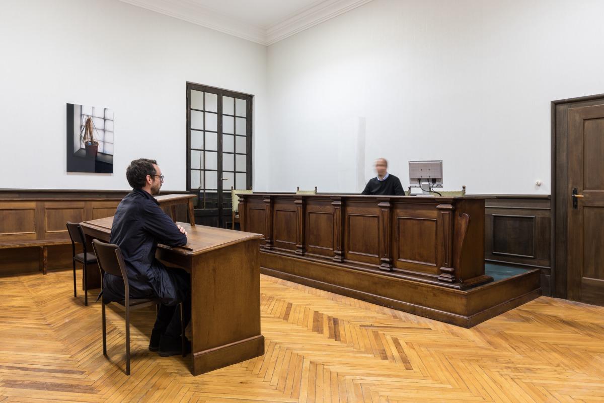 """מראה הצבה של """"הספינה דולפת. הקברניט שיקר."""" (אוצר: אודו קיטלמן), פונצדיונה פראדה:  אנה פיברוק, Courtroom (אולם משפט), 2017; במסך: אלכסנדר קולגה, Audiopassages (מעברי אודיו), 2017; על הקיר: תומס דימנד, Klause IV (Tavern IV), 2006 צילום: דלפינו סיסטו לגאני ו"""