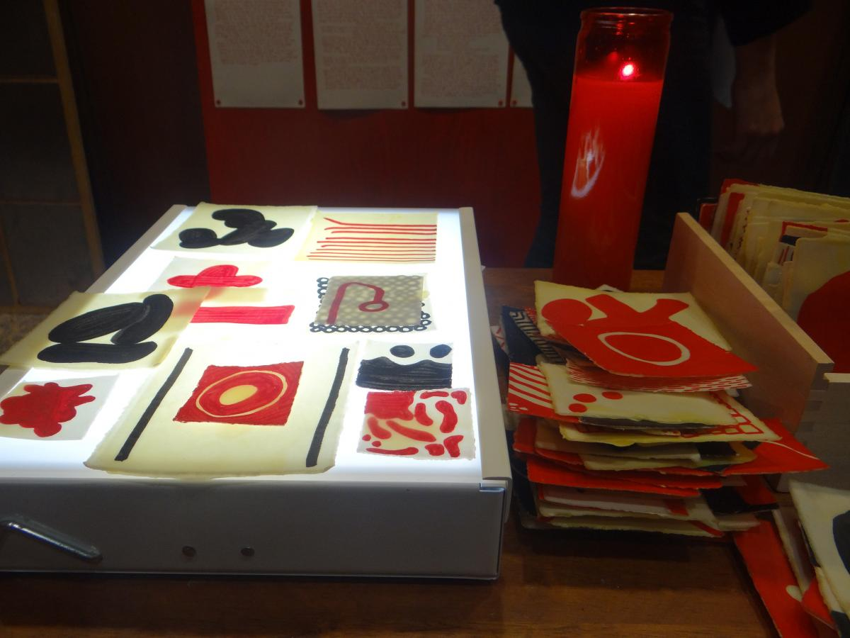 Josh T. France, In Tlilli, In Tlapalli: Three Tejanos in Red and Black (detail: Tejano/a Story-telling Table), 2013,  dinner tray, die-cut letters, beeswax-coated glyphs, light table, candle. Mulberry House, San Antonio. photo: Maya Cueva